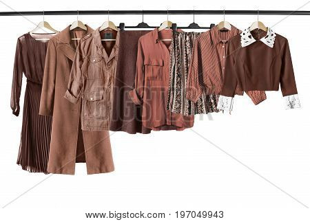 Set of brown woman clothes on clothes racks on white background