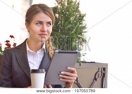 Pensive Young Woman Reading Her Touchscreen Tablet