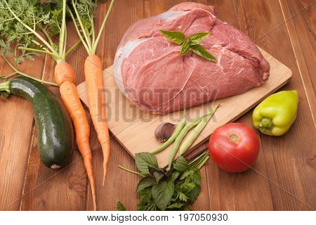 raw meat and vegetables on a cutting board