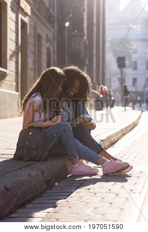 Two attractive girls sitting on the pavement and looking at the screen of the phone. one girl is african american. Beautiful city around.
