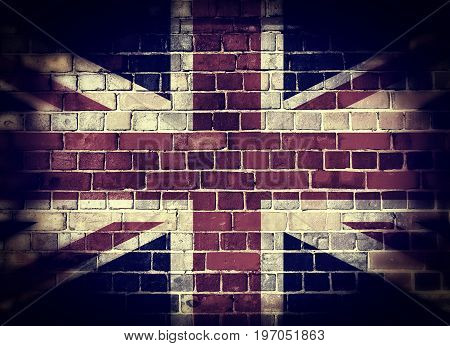 Desaturated Union flag on a brick wall background with a dark vignette