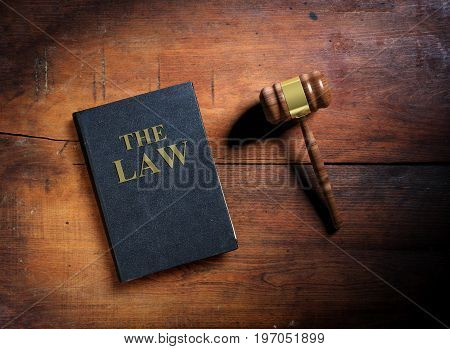 Law book and judge gavel on wooden background. 3d illustration