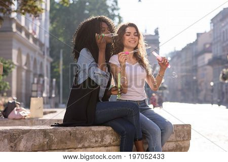 Two friends sitting on the street and blowing bubles