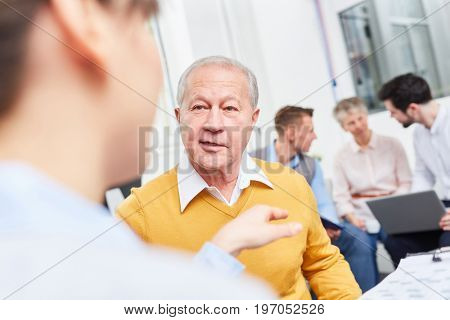 Consulting advice by businessman in senior team planning meeting