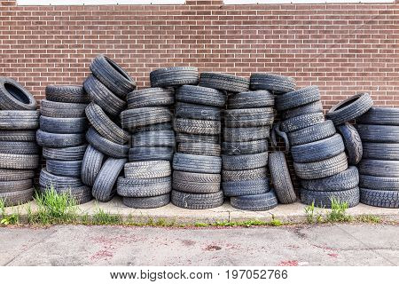 Pile of many old used tires against brick wall
