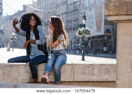 Two happy friends making selfie near the monument in the downtown. Casual lifestyle. One girl is black.