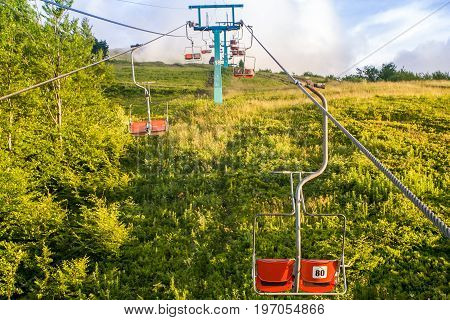 Mountain valley during sunset. View with ski lift chairs going far away to the clouds. Natural summer landscape in Carpathian mountains in Ukraine.