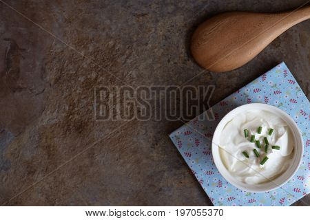 Sour cream is sprinkled with green onions on brown marble background. Top view with copy space