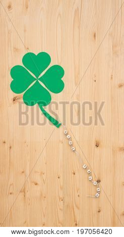 The german words for lot of success and a cloverleaf on a cord on wood