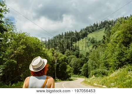 middle-aged woman with red hair in a hat walks on the road. Looks ahead at the mountains and forest.