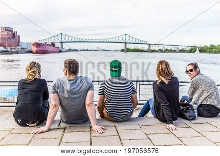 Montreal, Canada - May 27, 2017: People Sitting Looking At Jacques Cartier Bridge In Old Town In Cit