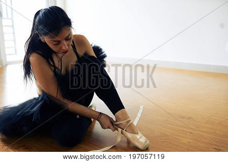 Beautiful middle-aged ballerina wearing black tutu skirt sitting on floor and putting on pointe shoes