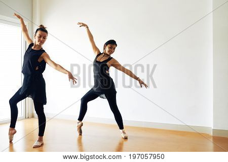 Two modern ballet dancers wearing leggings and tunics sharpening skills in spacious studio illuminated with daylight