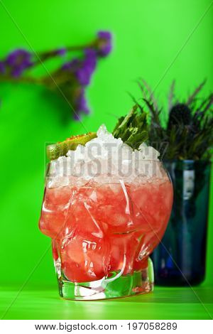 Halloween Cocktail - Zombie Cocktail on Bright Green Background. Zombie Cocktail made from Dark and Light Rums, Various Syrup, Grenadine, Grapefruit Juice, Lime Juice, Absinth