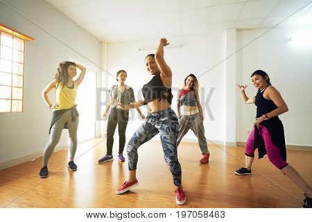 Cheerful women of different age gathered together in dance hall and learning hip-hop dance movement