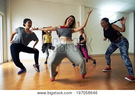 Full length portrait of pretty hip-hop dancer posing for photography with wide smile while standing on tiptoes, her colleagues dancing around her