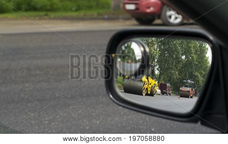 the reflection in the mirror of the repair of the road