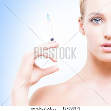 Young, beautiful and healthy woman having skin injections over blue background. Plastic surgery concept.