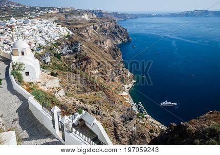 Fira, Thira town, Santorini Cyclade islands, Greece. Beautiful view of the town with white buildings, blue church's roofs and many colored flowers.