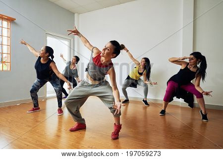 Group of energetic hip-hop dancers focused on training while gathered together in spacious dance hall