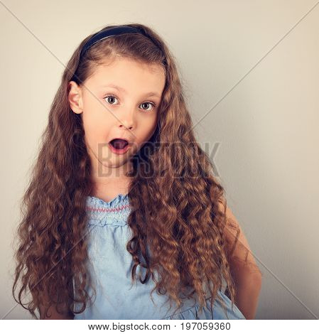 Excited Surprising Kid Girl With Long Curly Hair Style And Wide Open Mouth And Big Eyes Looking. Ton