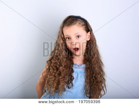 Excited Surprising Kid Girl With Wide Open Mouth And Big Eyes Looking On Blue Empty Copy Space Backg
