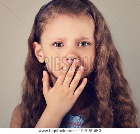 Unhappy Afraid Emotional Small Kid Girl With Teeth Pain Covering Hand The Mouth. Closeup Portrait. T