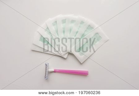Tool, instrument for hair depilation: razor and wax strips on a white background. Top. Close-up. Stock photo.