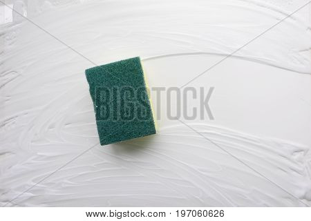 Lathered the sponge washes the soap surface. Abstract simple background, the backdrop of the subject of cleaning. White, light shades. Top view. Close-up. Stock photo