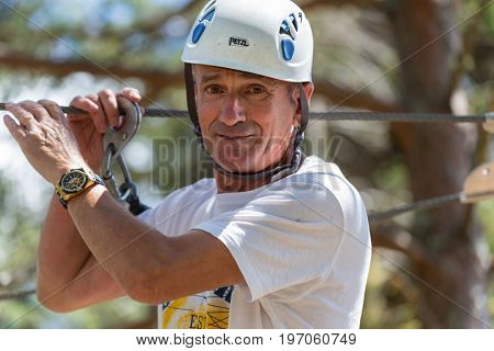 MEZIO, PORTUGAL - JULY 22, 2017: old adventurous man prepares to a slide in zip lining thru the forest. July 22, 2017, Mezio, Portugal.