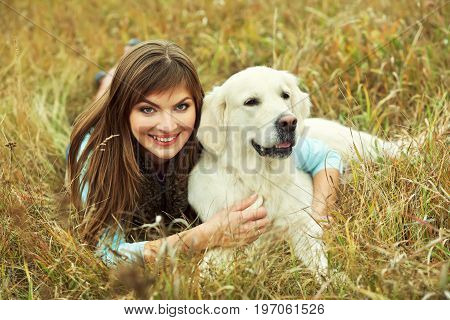 Young golden retriever for a walk with his owner. Dog breed labrador with woman outdoors
