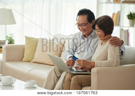 Cheerful elderly couple sitting on sofa and making purchases online