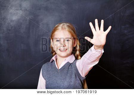 Portrait of a funny schoolgirl on blackboard background. School and education