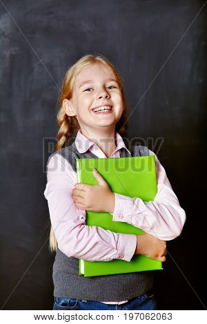 Portrait of a funny schoolgirl with a book on blackboard background. School and education