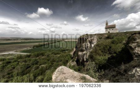 Romantic Drazovsky church on the hill Slovakia. Cloudscaoe over dark country.