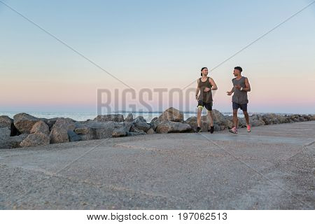 Two young sportsmen running together at the beach
