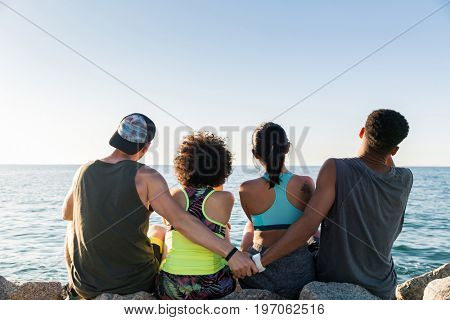 Back view of two young sporty couples sitting together and resting after work out outdoors