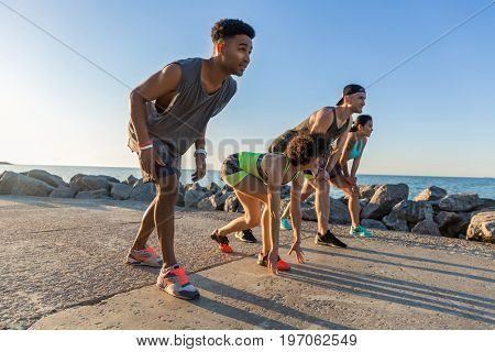 Group of sporty people getting ready to run a marathon at the beach