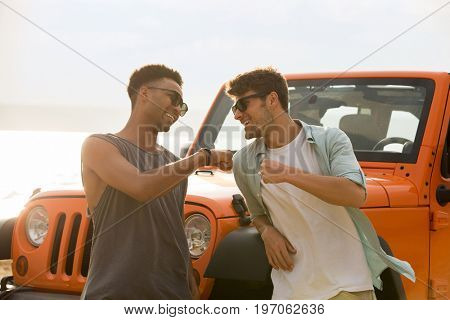 Two happy male friends having a good time together at the beach with a car on background
