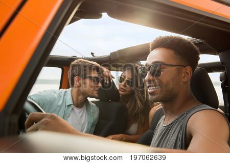 Group of multiethnic friends sitting in a car and having fun