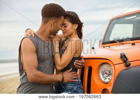 Lovely young couple kissing while standing near their car outdoors