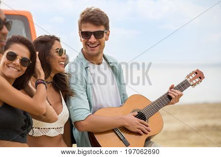 Group of happy smiling friends playing guitar and having fun together while standing at the beach