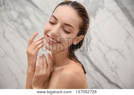 Young beautiful woman taking shower in bathroom