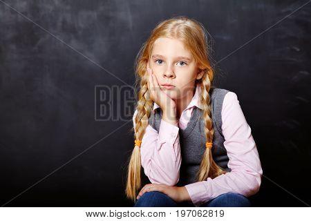 Portrait of a schoolgirl on blackboard background. School and education