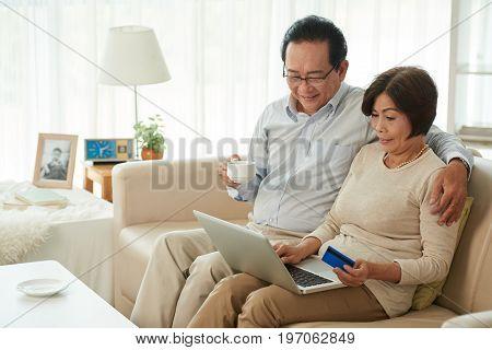 Smiling elderly Vietnamese couple drinking tea and shopping online