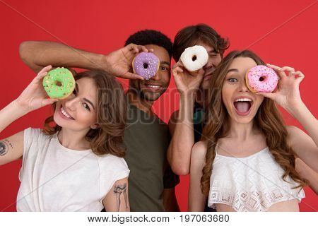 Picture of young cheerful group of friends friends standing with donuts isolated over red background. Looking at camera.