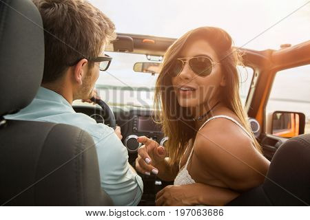 Joyful young couple smiling while sitting in their convertible car