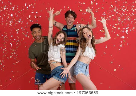 Photo of young cheerful group of friends standing isolated over confetti red background. Looking at camera.