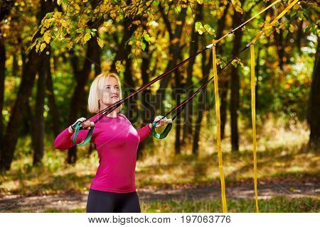 Young beautiful woman doing fitness training with suspension straps in park