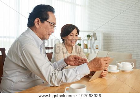 Vietnamese senior man showing something interesting on tablet computer to his wife